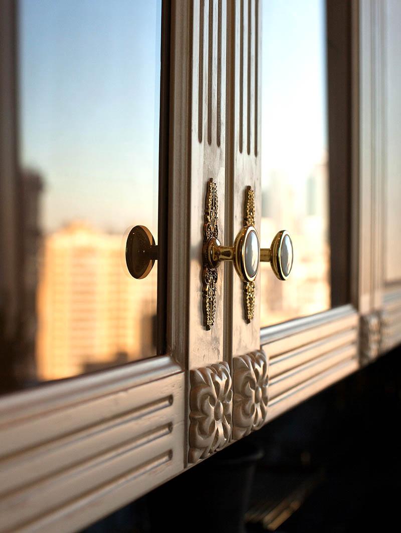 Фасады шкафчиков украшают ручки-кнопки с позолотой