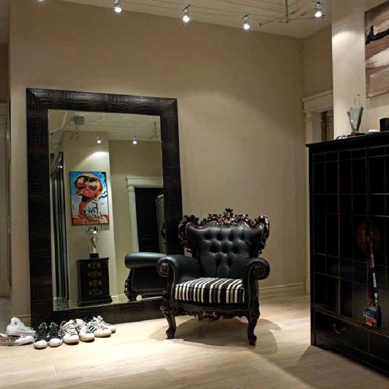 Главное место в прихожей занимает классическое кресло с полосатой шёлковой обивкой, спинка которого украшена ручной резьбой