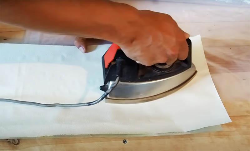 Полиэтиленовый рукав нужно заклеить по одному срезу. Это просто сделать, используя утюг и два листа бумаги. Для надёжности сделайте место склейки пошире, но не забудьте оставить посередине небольшое отверстие для того, чтобы вставить трубу
