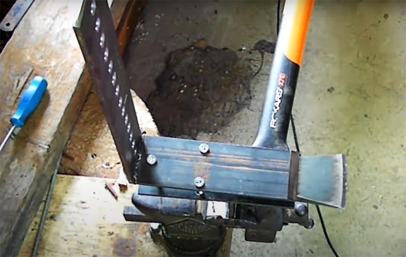 Нижняя часть конструкции фиксируется в тисках, детали между собой соединяются тремя болтами и между ними вставляется топор. Закрутите болты для надёжной фиксации лезвия перед заточкой