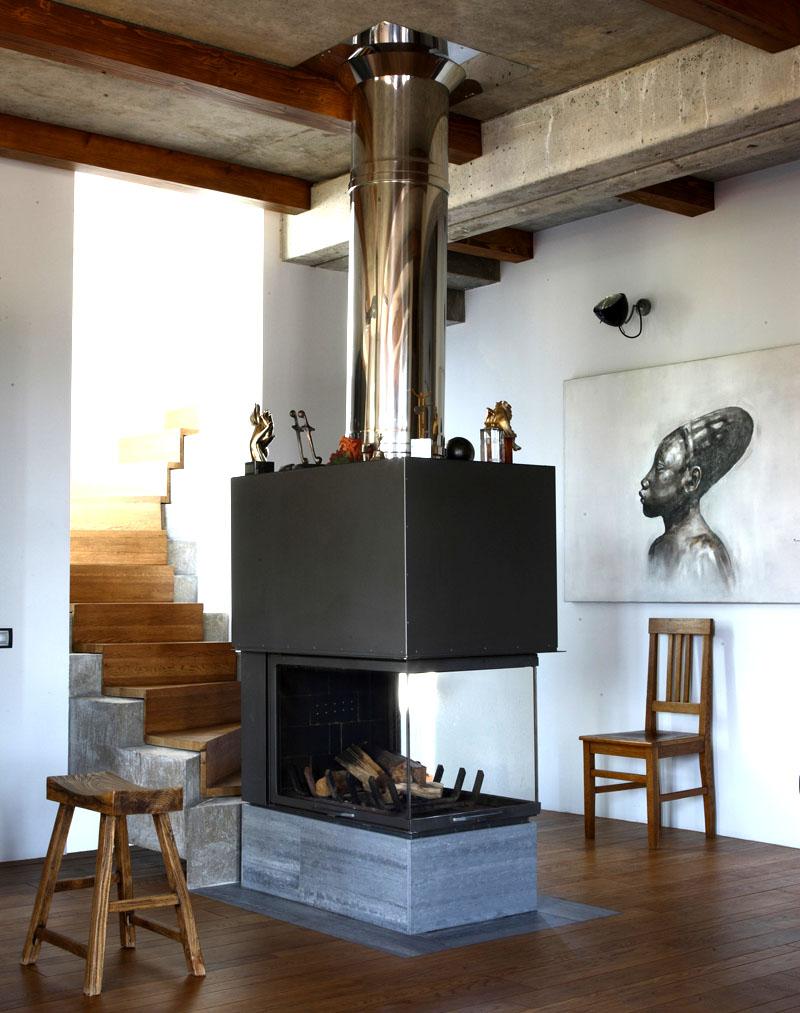 Возле лестницы на подиуме из натурального камня установили стильный камин с дымоходом