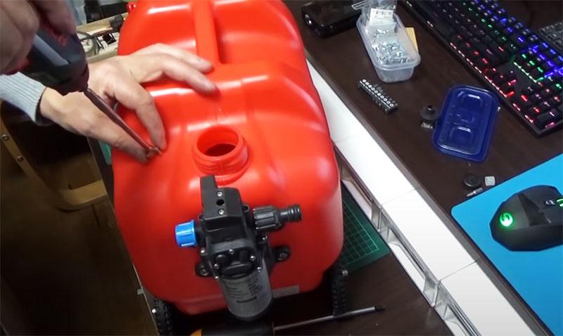 Следующий этап – организация подачи воды из канистры в компрессор. Для этого в корпусе канистры сверху нужно сделать ещё одно отверстие под шланг. Снова понадобится дрель или горячая спица. И если есть возможность – используйте уплотнительное резиновое кольцо. Шланг нужно опустить на дно канистры, чтобы прибор расходовал воду до последней капли
