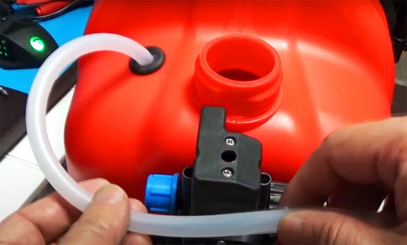 Шланг опускается на дно так, чтобы он лёг, а второй конец фиксируется на компрессоре. Теперь можно подсоединить шланг с пистолетом в выходное отверстие компрессора