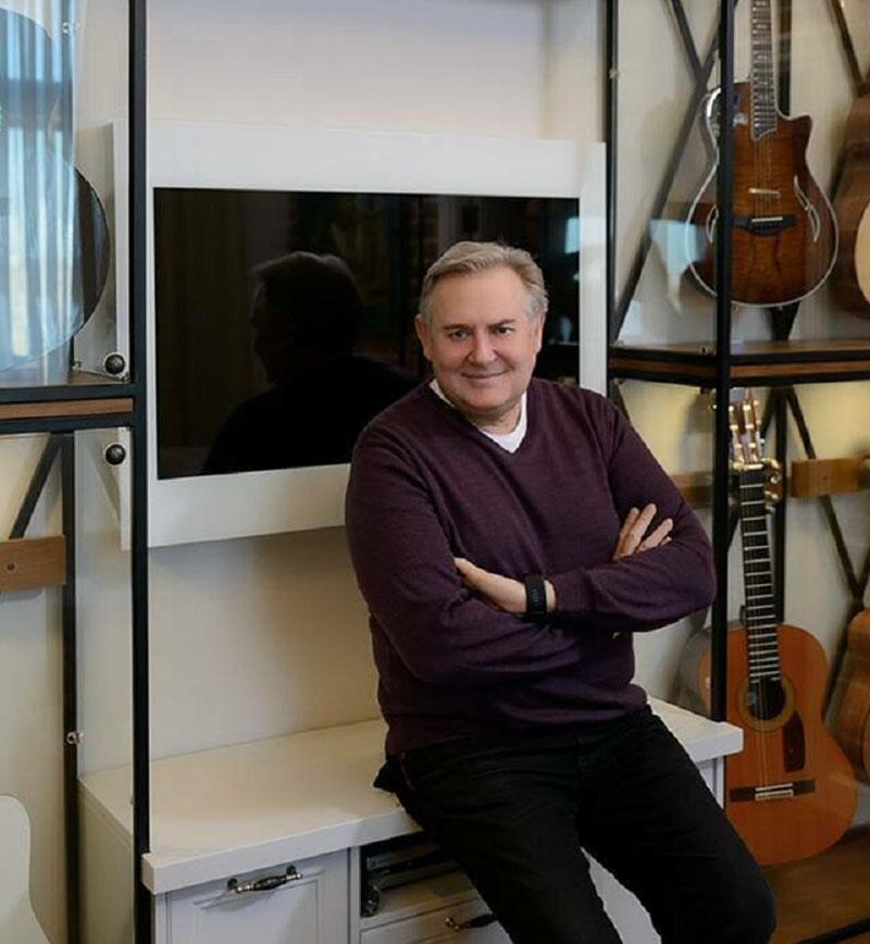 На стене между витринами для гитар повесили небольшую плазму