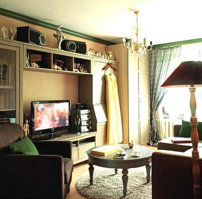 Для оформления окна выбрали белоснежный тюль и портьеры приглушённого зелёного оттенка с принтом