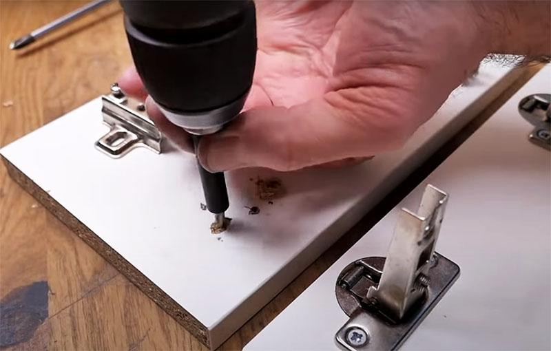 Чтобы вставить мебельный крепёж, нужно рассверлить повреждённое отверстие. Используйте ограничитель на сверло, чтобы не проткнуть дверцу насквозь. Это может быть даже простая пластиковая трубка от фломастера, как у автора