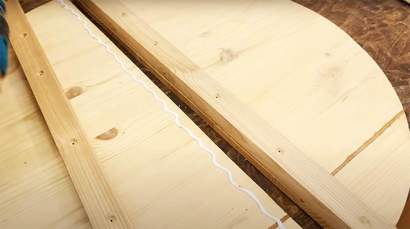 Место соединения двух половинок стола с нижней стороны фиксируется на два куска бруса. Крепежи устанавливайте со стороны бруса, чтобы на «парадной» части столешницы они были незаметны. Не забудьте предварительно просверлить отверстия под саморезы, чтобы брус не треснул во время работы, и раззенковать, чтобы утопить шляпку