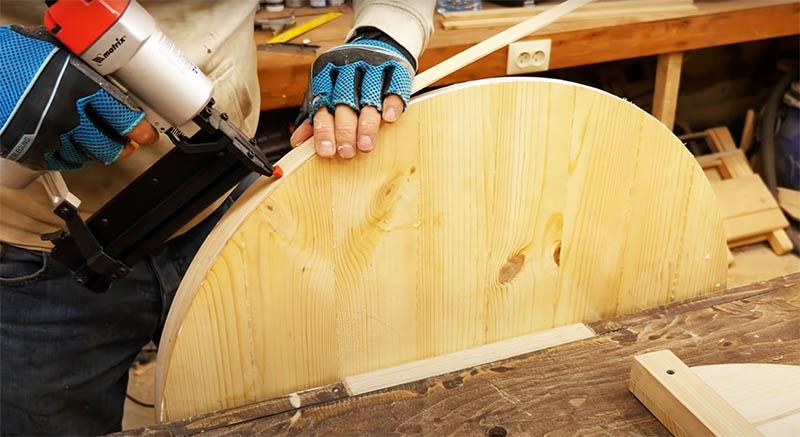 Внешний край столешницы оформляется деревянным шпоном. Автор нарезал на станке полосы из бруса толщиной примерно 4-5 мм. Такие полосы легко гнутся. Он закрепил их в несколько слоёв по краю, скрепляя шпильками и клеем ПВА. Ширина полос – около 6 см, они шире, чем толщина столешницы. Когда все слои края зафиксированы и просохли, можно заполнить щели, если они есть, шпаклёвкой по дереву и отшлифовать
