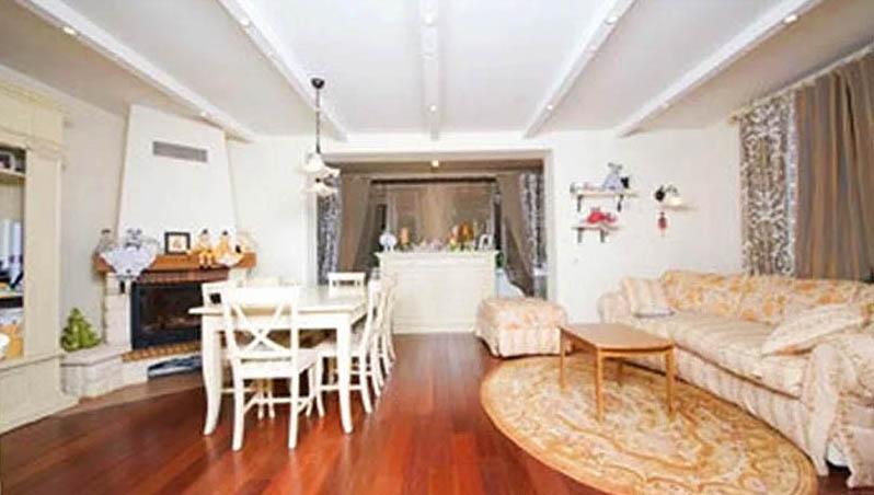 Возле окна обустроили зону отдыха с роскошным диваном, креслом и пуфиком, перед которыми постелили классический овальный ковёр