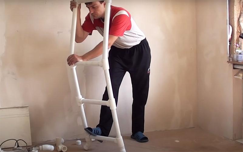 Верхний поручень стремянки нужно слегка согнуть под углом примерно в 20°. Для этого пластик следует нагреть и прямо в тройнике потянуть на себя, придавая конструкции необходимую форму. Когда трубы остынут, они сохранят этот изгиб