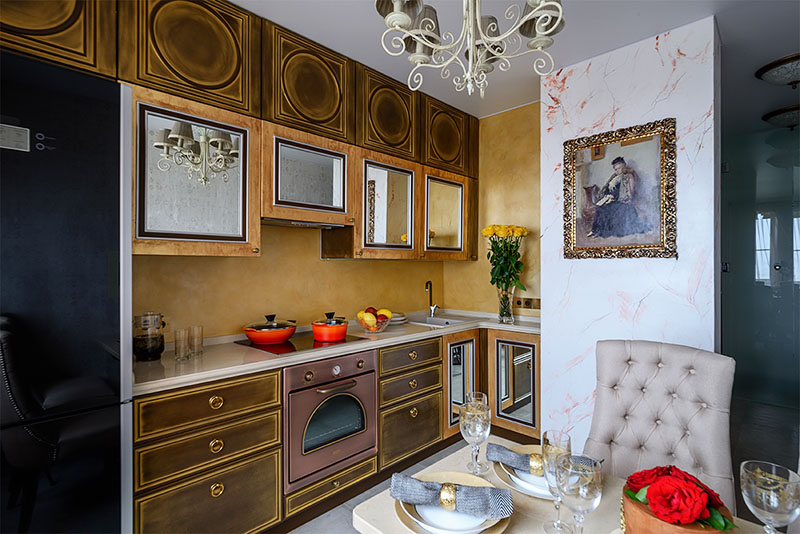 Духовой шкаф в ретростиле цвета медь и чёрная стеклокерамическая варочная поверхность идеально вписались в стильный интерьер кухни