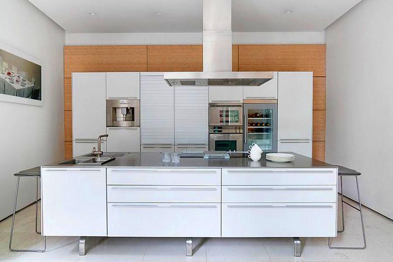 Холодность хрома смягчает деревянная панель на задней стенке кухни