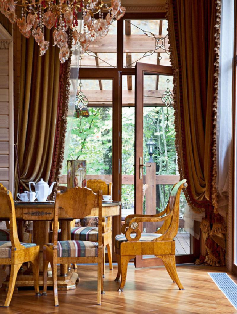 Столовую зону освещает роскошная люстра с подвесками-листиками из цветного хрусталя