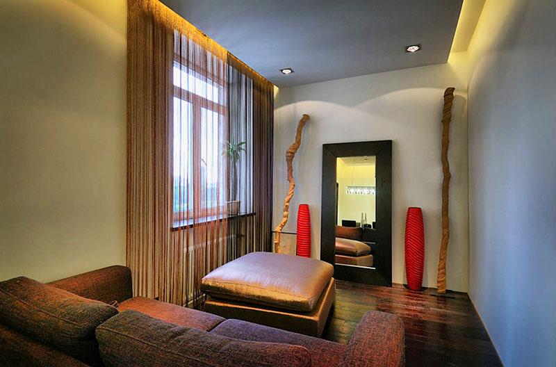 Интерьер гостиной выполнен в монохромной гамме и украшен яркими акцентами в виде алых ваз