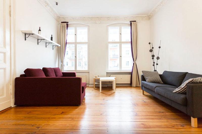 Светлая отделка, большие окна, высокие потолки и минимум мебели визуально делают гостиную немного просторнее