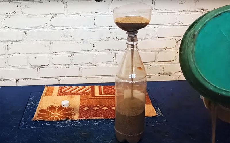 Песком нужно заполнить бутылку. Используйте для этого воронку, кстати, её можно сделать из такой же бутылки