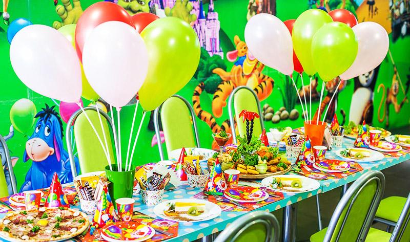 Стол для детей можно украсить шарами, допустимо использовать одноразовую яркую посуду, ведь малыши могут веселиться так, что всё будет разлетаться в разные стороны