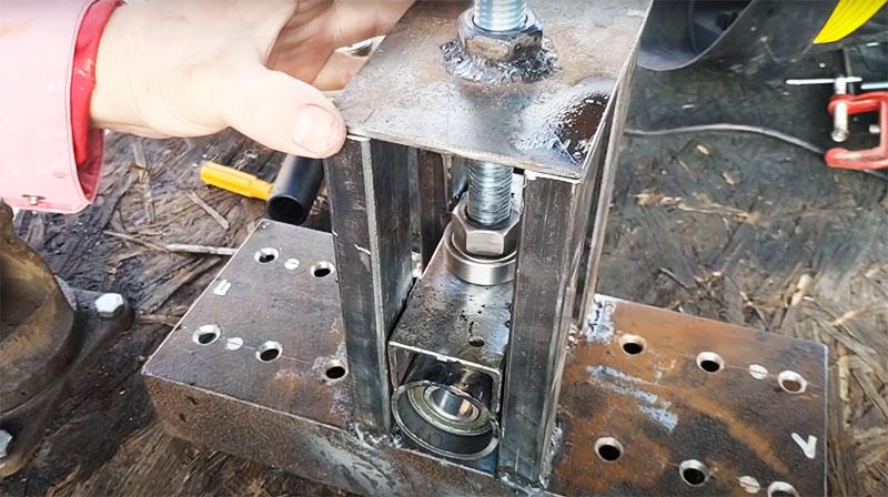 Сквозь верхнюю пластину нужно сделать прорезь для винтовой шпильки и приварить к ней гайку, а к п-образному основанию центрального ролика тоже приваривается гайка. Шпилька проходит сквозь верхнюю платформу и фиксируется в основании ролика в гайке
