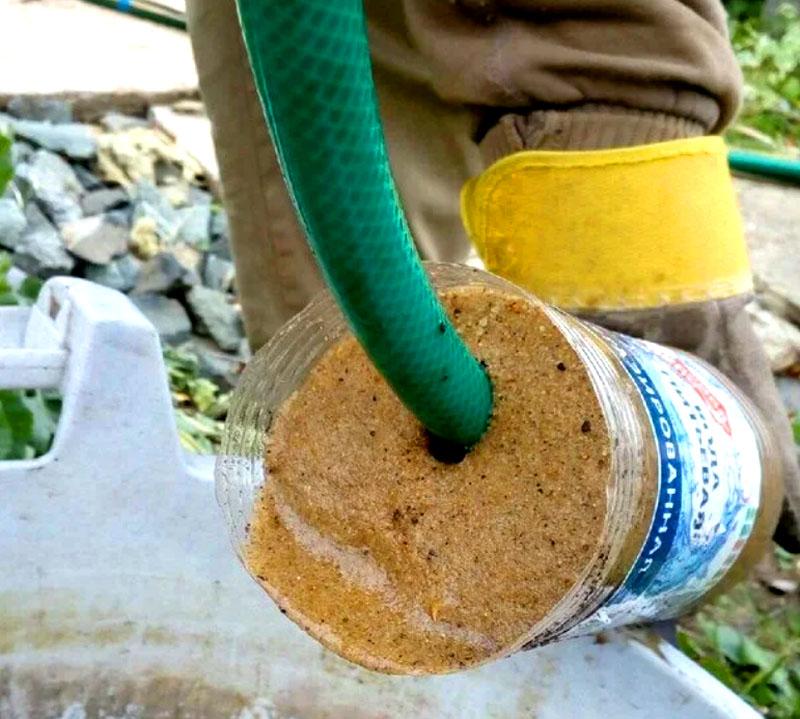 Поток воды будет размывать песок, и он осядет в бутылке. Периодически вынимайте шланг с бутылкой из скважины для очистки