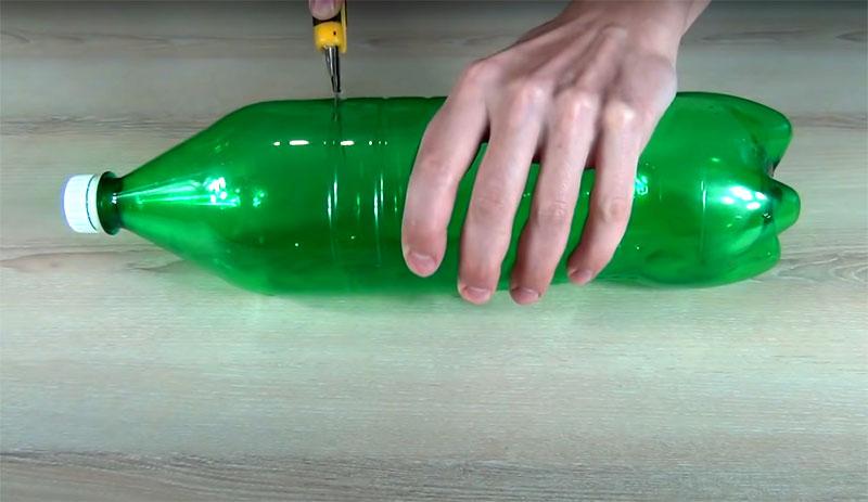 Её нужно разрезать пополам поперёк и вставить горлышко в низ бутылки‒ в часть с донышком. Вверху можно зафиксировать любым удобным для вас способом ‒ скотчем, обычным канцелярским степлером ‒ или просто спаять горячей спицей