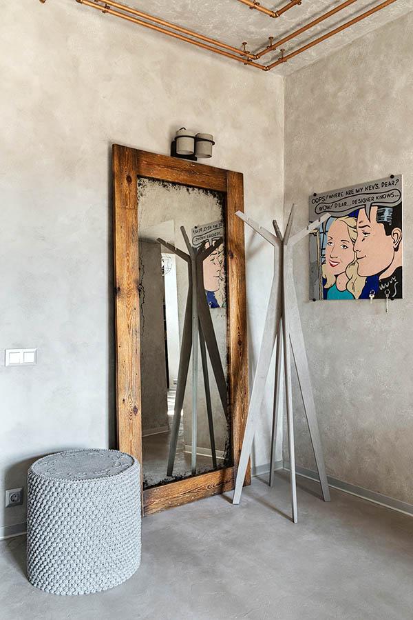 В холле поставили большое зеркало в деревянной раме и повесили юмористический шарж на хозяев квартиры, который смягчил строгость интерьера