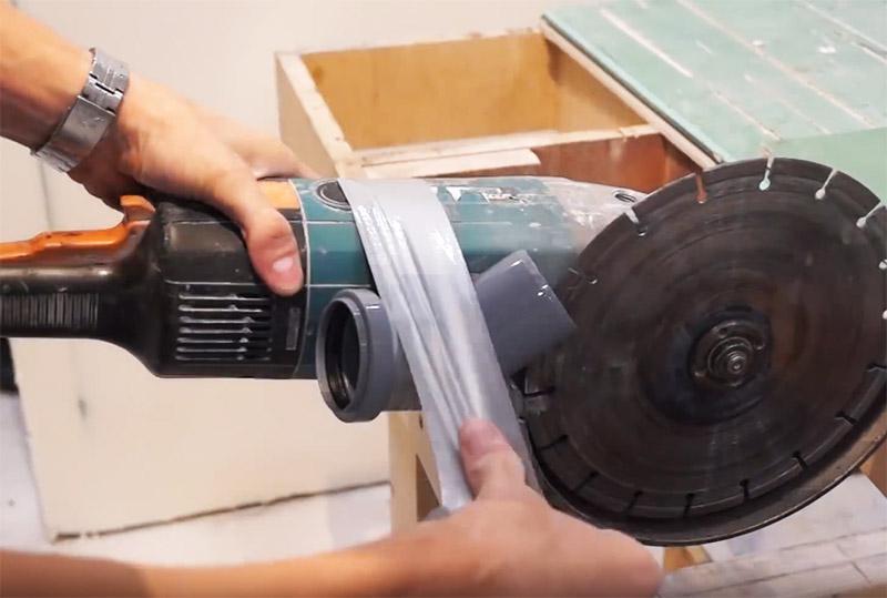 Готовый патрубок крепится на болгарке с заходом на диск. Прочно зафиксируйте деталь на корпусе инструмента несколькими мотками армированного скотча. От его надёжной фиксации зависит весь успех предприятия. Диск не должен во время работы цеплять муфту