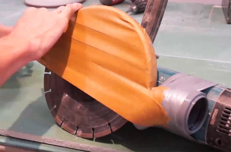 Чтобы направить поток пыли в патрубок, нужно доработать существующий кожух инструмента. На него наклеивается скотч так, чтобы скрыть расположение диска наполовину. Диск при этом свободно вращается, потому что скотч клеится не на него, а на обод кожуха