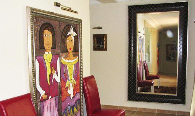 Дополняет оформление гостиной огромное зеркало в раме, обтянутой натуральной кожей