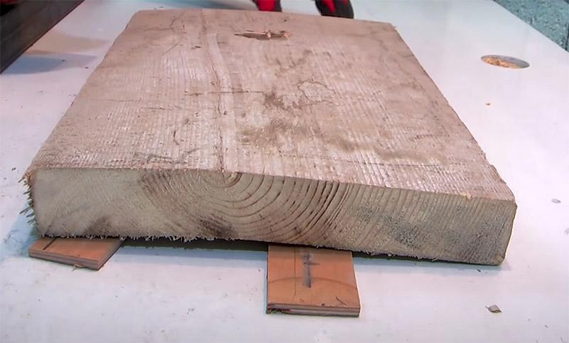 Обрезки фанеры или ДВП помогут выровнять доску и уложить её плотно на верстаке