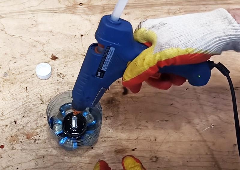 После фиксации болта крышку нужно заполнить клеем. Проблема только в том, что термоклей может расплавить крышку. Избежать этого поможет простой трюк: крышку с болтом нужно поместить в ёмкость с водой так, чтобы вода не доходила до краёв. А потом заполняйте крышку клеем, температура уже не будет достаточной для деформации