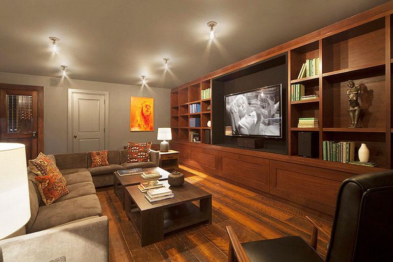 Освещают комнату точечные потолочные светильники и невысокие дизайнерские настольные лампы
