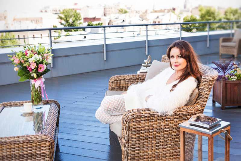 Оксана поставила на террасе комфортную мебель из натурального ротанга и деревянные кашпо с живыми цветами