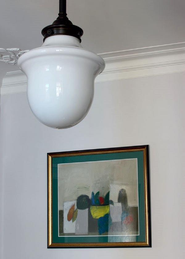 Гостиную освещает необычный светильник с плафоном из белого стекла в стиле 20-х годов прошлого столетия