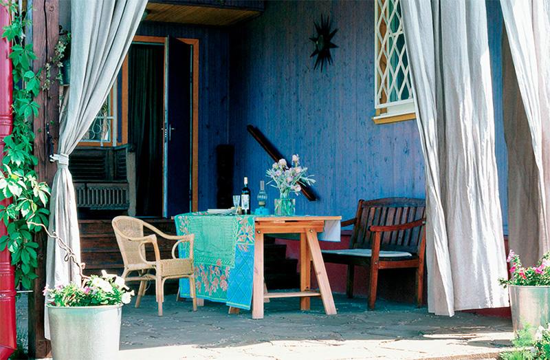 На веранде обустроили комфортную зону отдыха с удобными креслами из ротанга и массива