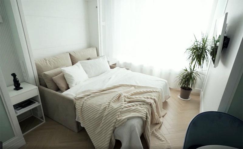 Весь секрет дивана в том, что он необычный. На самом деле это кровать-трансформер, которая в собранном виде прячется в стенной нише, а потом благодаря паре лёгких движений и пружинному механизму превращается в полноценную двухспальную кровать