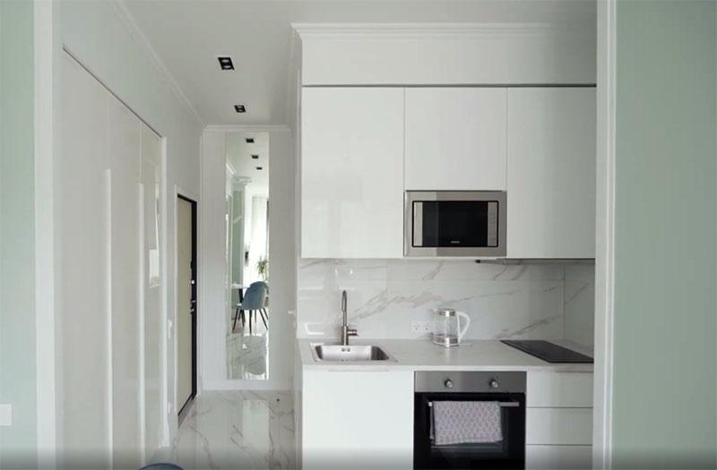 Компактная кухня тоже расположена так, что кажется единым целым с окружающим пространством. Здесь зазор с коробом в верхней части сделали в 2 сантиметра, иначе было невозможно подвесить полки