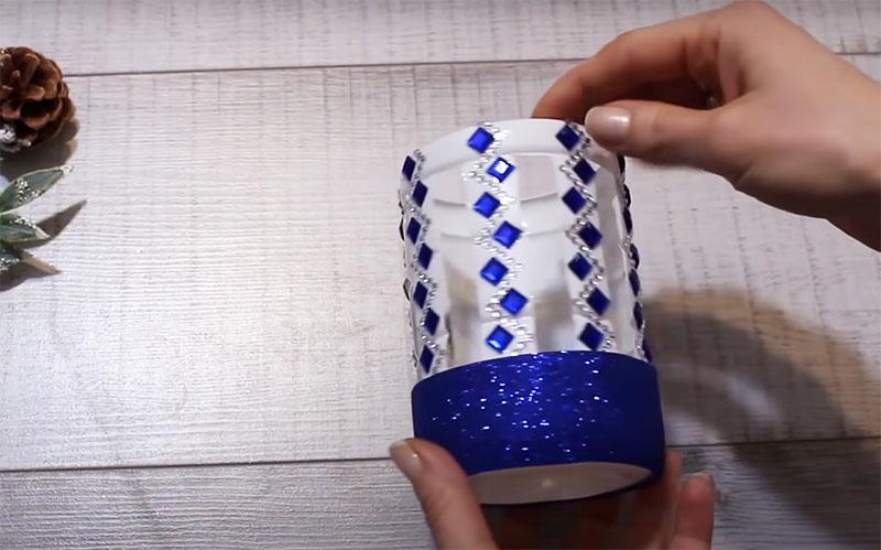 Нижнюю часть бутылки украсьте полоской блестящей бумаги, фольгой или другим материалом. Можно использовать тесьму, кружево, одним словом, всё, что, на ваш взгляд, подойдёт для украшения