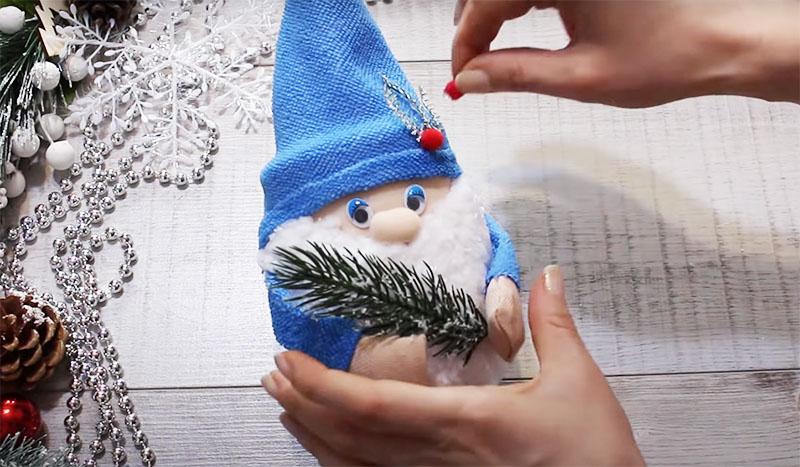 Для декора новогоднего гнома используйте хвойные веточки, ёлочные игрушки, бусины и перья