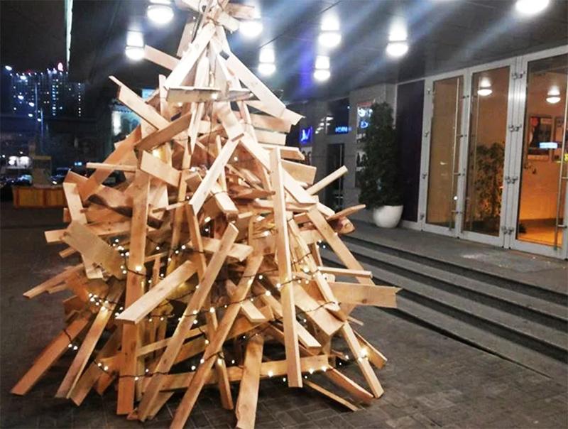 Доски или самые обычные дрова тоже могут превратиться в новогоднее дерево. Причём совсем не обязательно крепить их в каком-то правильном порядке. Главное – набросить гирлянду
