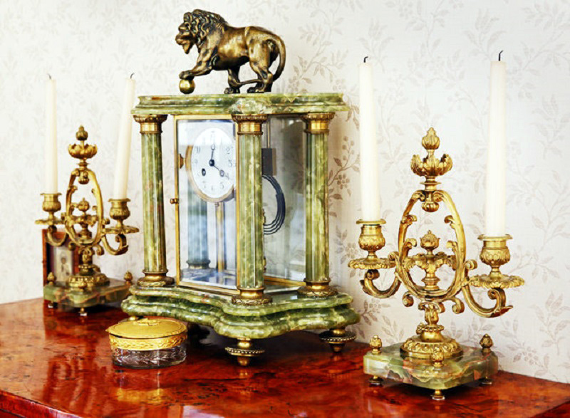 Столешницу комода украшают антикварные подсвечники в позолоте и старинные механические часы с ручным заводом