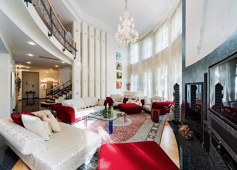 Освещает просторную гостиную многоярусная люстра с хрустальными капельками-подвесками и лампочками-свечками