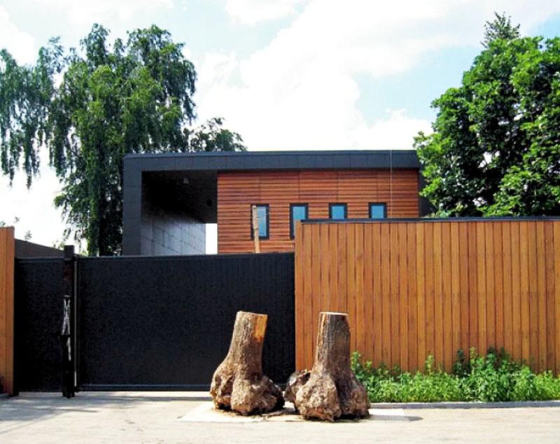 Дом со всех сторон ограждён высоким деревянным забором, входную зону украшает парочка выкорчеванных и обработанных деревьев
