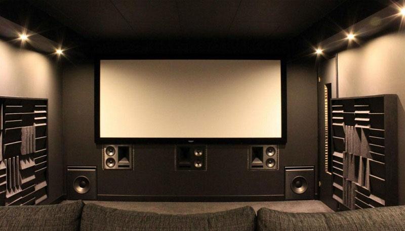 Напротив экрана стоит огромный диван с регулируемой спинкой и удобными подушками