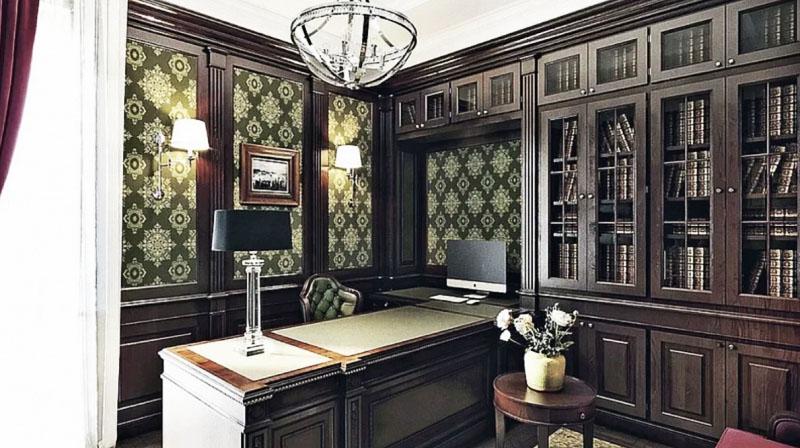 Освещают кабинет стильная люстра с хромированным каркасом в виде полусферы и классические бра с тканевыми абажурами