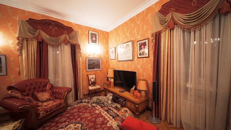 На пол в гостиной постелили классический ковёр бордового цвета со светлым орнаментом
