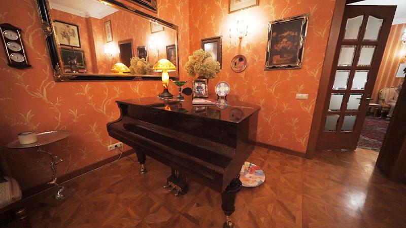 Перед гостиной оформили настоящий музыкальный салон с классическим чёрным роялем