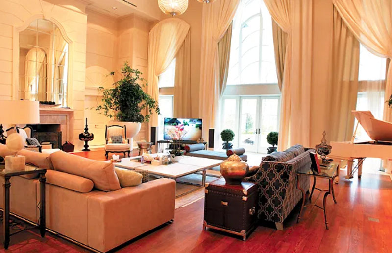 Освещают пространство ряд точечных светильников над каждой функциональной зоной гостиной и роскошная люстра с хрустальными подвесками