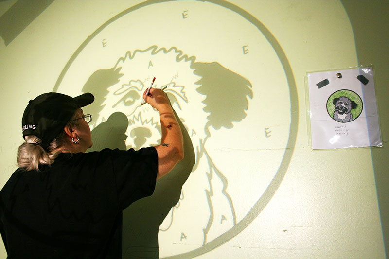 Закрепите распечатку рисунка на тонкой бумаге на лампе и направьте проекцию на стену. Теперь можно взять карандаш и перенести изображение