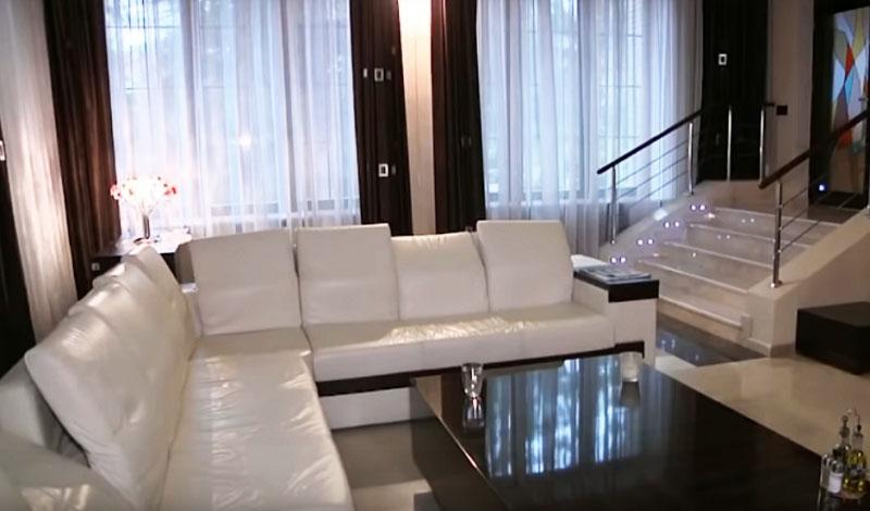 Огромные окна украшены белоснежным тюлем и однотонными шторами тёмно-шоколадного оттенка