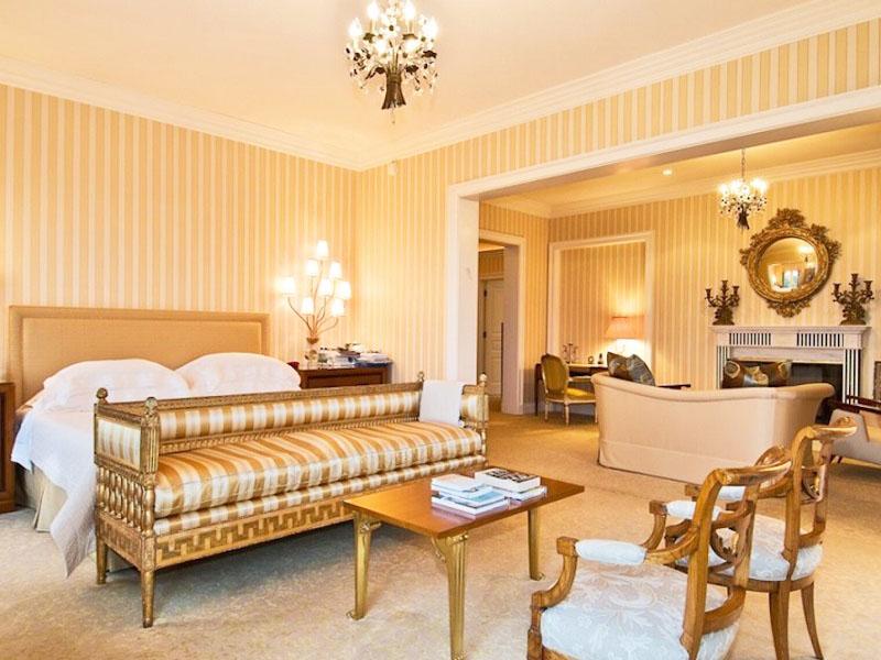 Освещают спальню дизайнерские люстры в виде деревьев с веточками светодиодов и изящная настольная лампа с россыпью небольших абажуров